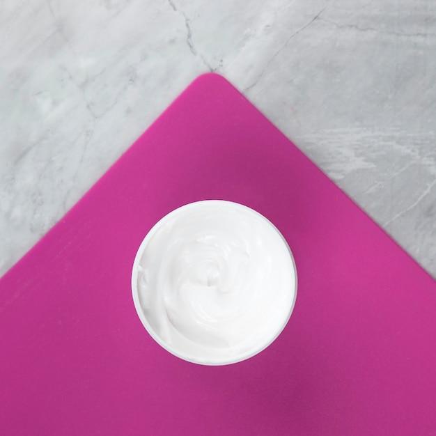 Vue rapprochée d'une crème sur fond rose et marbre Photo gratuit