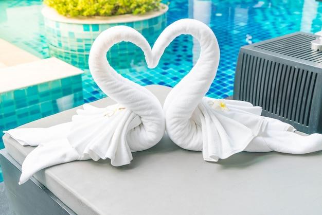 Vue rapprochée de deux jolies serviettes de cygne au lit Photo gratuit