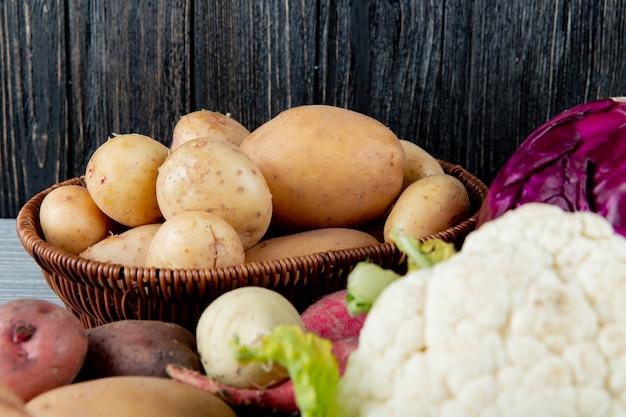 Vue Rapprochée Du Panier Plein De Pommes De Terre Avec D'autres Légumes Autour Sur Fond De Bois Avec Copie Espace Photo gratuit