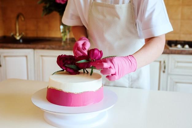 Vue Rapprochée Du Pâtissier Décore Un Gâteau Appétissant Avec Des Pivoines. à L'intérieur Dans La Cuisine. Dessert Maison Pour Les Vacances. Photo Premium