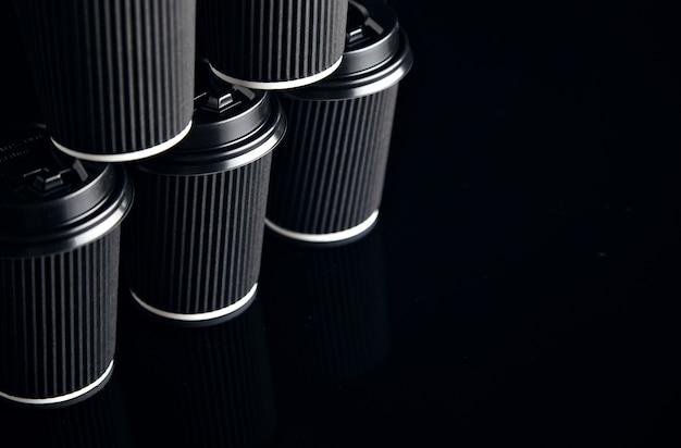 Vue Rapprochée Sur Un Ensemble Non étiqueté De Gobelets En Carton à Emporter Noir Fermé Avec Des Bouchons En Forme De Pyramide Présentés Sur Le Côté Photo gratuit
