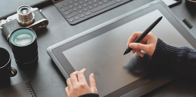 Vue rapprochée de la femme designer s'appuyant sur une tablette dans un lieu de travail élégant et sombre Photo Premium