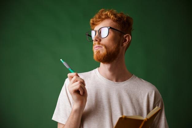 Vue Rapprochée De La Pensée D'un Jeune Homme Barbu En T-shirt Blanc Tenant Un Cahier Et Un Stylo Photo gratuit