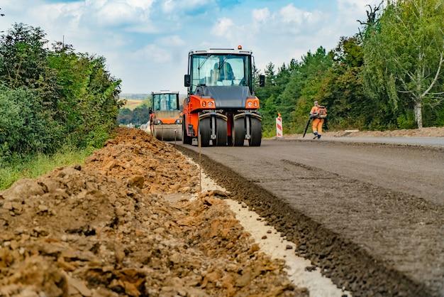 Vue rapprochée sur les rouleaux de la route travaillant sur le nouveau chantier de construction de la route Photo Premium
