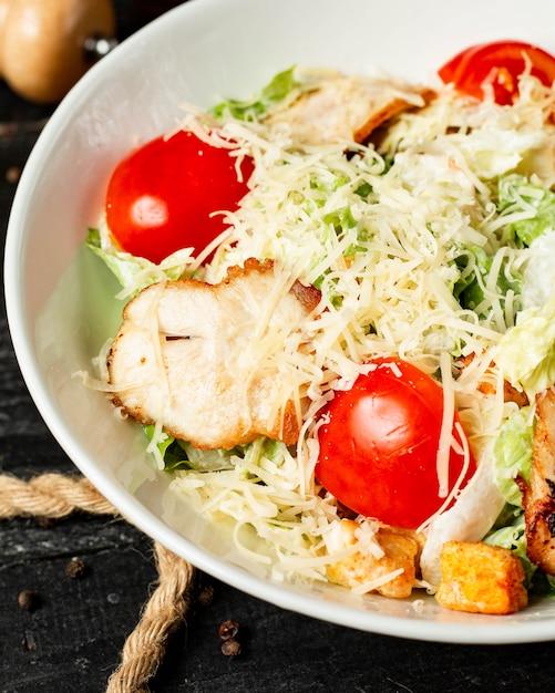 Vue Rapprochée De La Salade César Avec Des Tomates Au Poulet Et Du Parmesan Dans Un Bol Photo gratuit