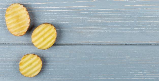 Vue Rapprochée De Tranches De Pommes De Terre Tranchées Et ébouriffées Sur Le Côté Gauche Et Fond En Bois Avec Copie Espace Photo gratuit