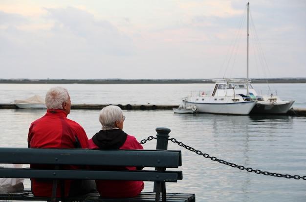 Vue rapprochée d'un vieux couple solitaire sur le banc en regardant l'océan. Photo Premium