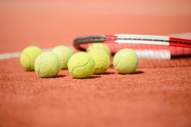 Vue de la raquette de tennis et des balles sur le court de tennis en terre battue. Photo Premium
