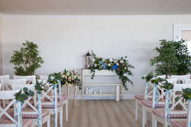Vue d'une scène de cérémonie de mariage dans une pièce avec plusieurs rangées de chaises blanches et des compositions Photo Premium