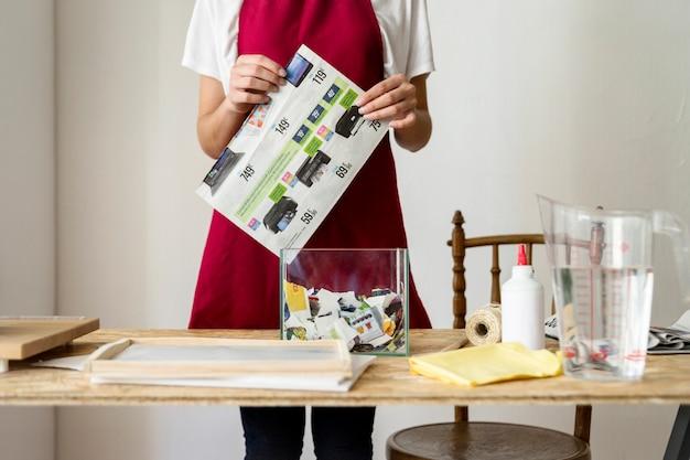 Vue de la section médiane d'une femme tenant le papier derrière un bureau en bois Photo gratuit