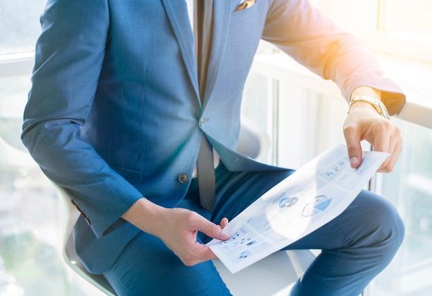 Vue de la section médiane de la main d'un homme d'affaires sur feuille infographique Photo gratuit