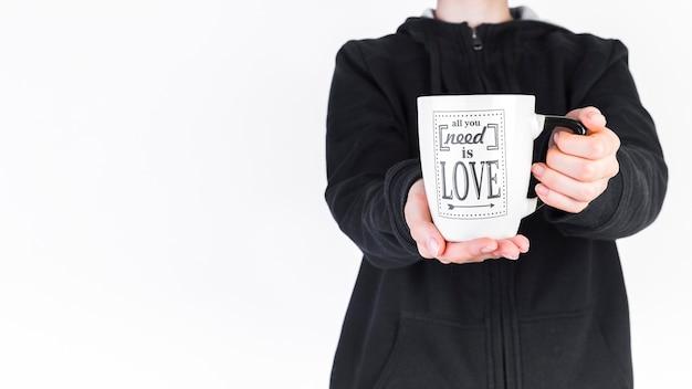 Vue de la section médiane d'une personne tenant une tasse blanche avec tout ce dont vous avez besoin est le texte d'amour Photo gratuit