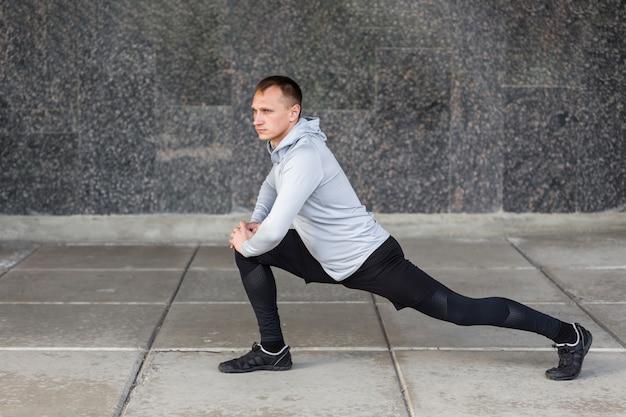 Vue sportive homme faisant des exercices d'échauffement Photo gratuit