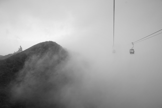 La vue de la statue de big buddha sur la colline de montagne à hong kong dans un jour de brouillard. Photo Premium