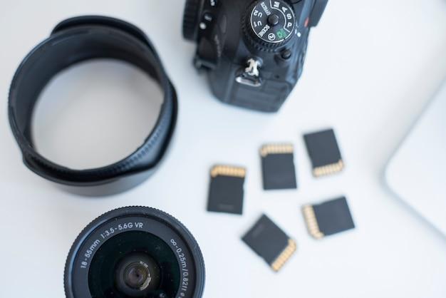 Vue surélevée des accessoires de l'appareil photo avec cartes mémoire sur le bureau Photo gratuit