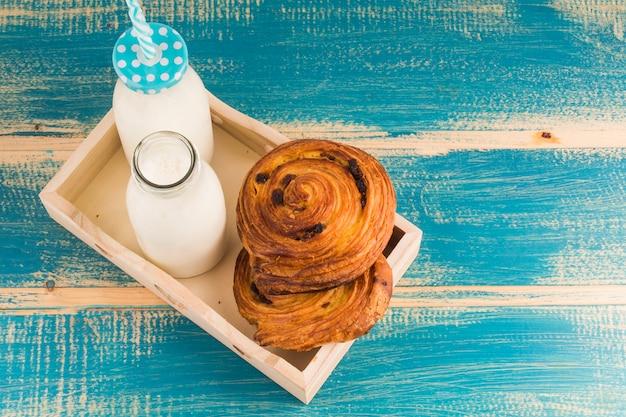 Vue surélevée de bouteilles de lait et de pâtisseries françaises sucrées dans un plateau en bois sur une table bleue Photo gratuit