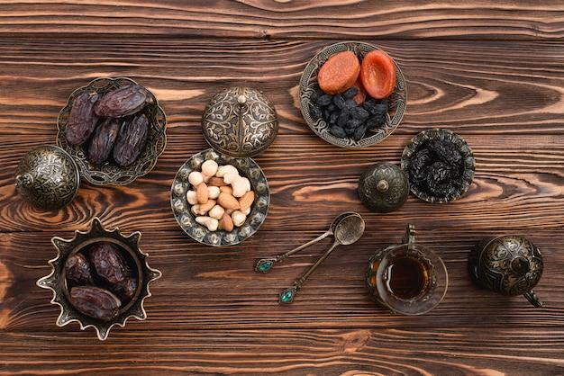 Une vue surélevée de dattes fraîches du ramadan; des noisettes; fruits secs et thé sur un bureau en bois Photo gratuit