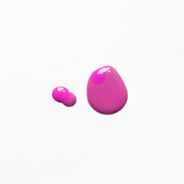 Vue surélevée de déversement de vernis à ongles rose sur fond blanc Photo gratuit
