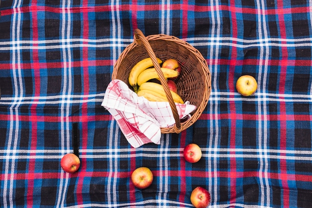 Une vue surélevée du panier de pique-nique avec des bananes et des pommes sur une couverture Photo gratuit