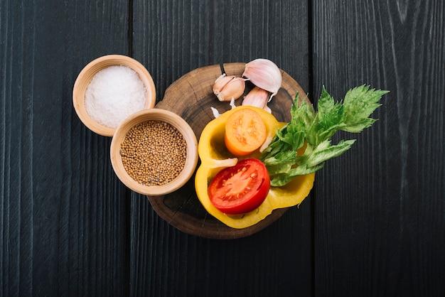 Vue surélevée d'épices et d'ingrédients sur un fond en bois texturé noir Photo gratuit