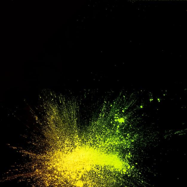Vue surélevée d'explosion de poudre de couleur jaune sur fond noir Photo gratuit