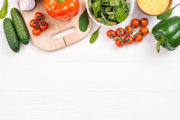 Une vue surélevée de légumes frais sur un bureau en bois blanc Photo gratuit