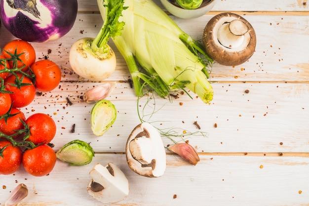 Vue surélevée de légumes frais et de flocons de piment rouge sur fond en bois Photo gratuit