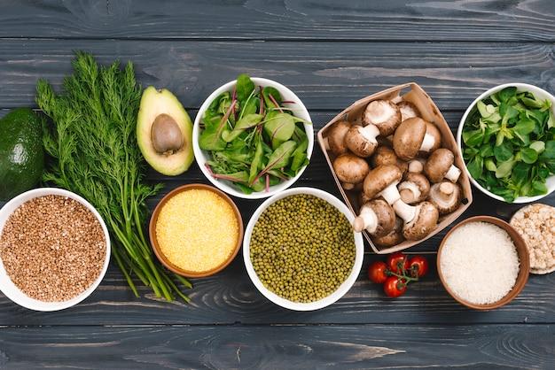Une vue surélevée de légumes frais et de légumineuses sur un bureau en bois noir Photo gratuit