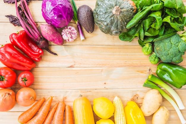 Vue surélevée de légumes sains formant un cadre circulaire sur fond en bois Photo gratuit