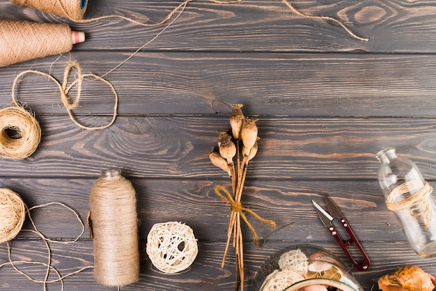 Vue surélevée de matériel artisanal avec des gousses de pavot attachées et une bouteille en verre Photo gratuit