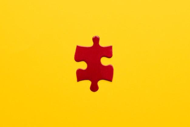 Vue surélevée d'une pièce de puzzle rouge sur fond jaune Photo gratuit