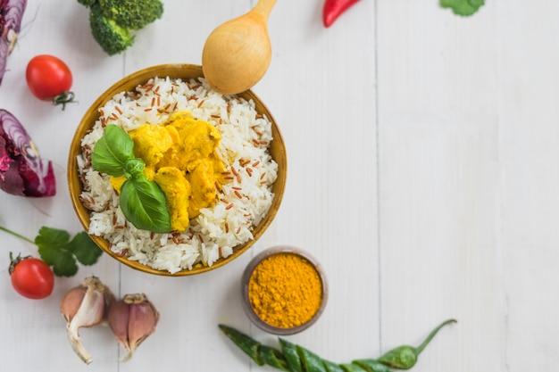 Vue surélevée de riz frit au poulet et feuilles de basilic avec des ingrédients sur fond blanc Photo gratuit