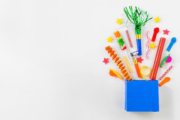 Vue surélevée de sac en papier avec divers accessoires de fête sur fond bleu Photo gratuit