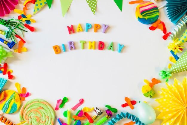 Vue surélevée de texte joyeux anniversaire avec des accessoires de fête sur une surface blanche Photo gratuit