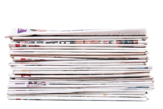 Vue d'un tas de journaux empilés isolé sur fond blanc. Photo Premium