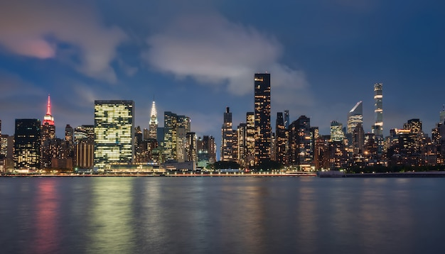 Vue Sur Les Toits De Manhattan, New York, Usa, La Nuit, Depuis La Zone Dumbo. Photographie Longue Exposition, Avec Des Reflets Dans L'eau Avec Une Texture De Soie D Photo Premium