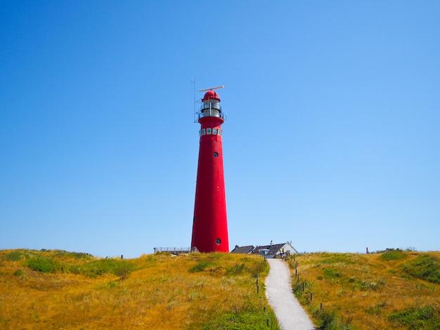 Vue de la tour nord - phare des îles schiermonnikoog, une des îles frisonnes, sur une dune de sable sur fond de ciel bleu Photo Premium