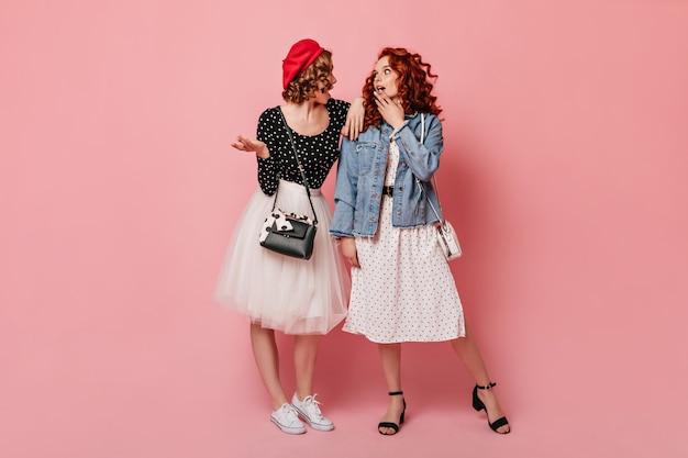 Vue Sur Toute La Longueur De Deux Filles élégantes Parlant Sur Fond Rose. Prise De Vue En Studio De Dames Gracieuses. Photo gratuit