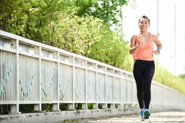 Vue de toute la longueur du jeune jogging faisant une course matinale seul Photo gratuit