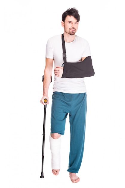 Vue de toute la longueur d'un jeune homme avec une jambe cassée. Photo Premium