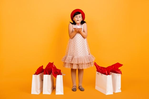 Vue Sur Toute La Longueur De La Petite Fille D'anniversaire Posant Après Le Shopping. Enfant Souffle La Bougie Sur Le Gâteau. Photo gratuit