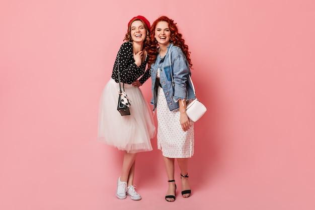 Vue Sur Toute La Longueur Des Sœurs Heureuses Riant à La Caméra. Photo De Studio De Filles à La Mode Posant Sur Fond Rose Avec Le Sourire. Photo gratuit