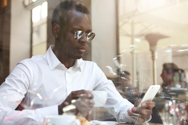 Vue à Travers La Vitre De La Belle Bisunessman Noir Ou Travailleur D'entreprise Portant Des Nuances Rondes Et Chemise Formelle De Boire Du Café Et De Vérifier Les E-mails Sur Téléphone Mobile Pendant La Pause Au Café Moderne Photo gratuit