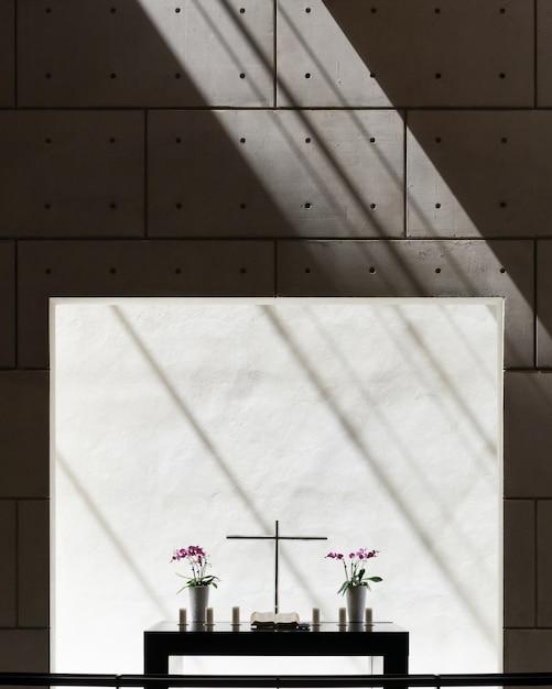 Vue Verticale Des Vases Et Une Croix Sur Une Table Dans Une Pièce Avec Mur En Béton Photo gratuit