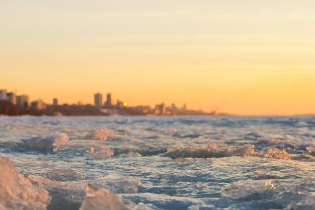 Vue de la ville au début du printemps au coucher du soleil avec la banquise au premier plan et la ville Photo Premium