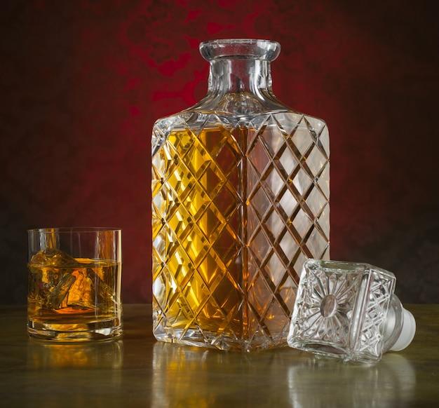 Whisky en bouteille et verre avec glace Photo Premium
