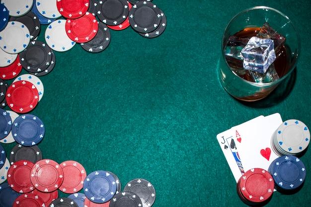 Whisky avec des glaçons et des jetons de casino et une carte à jouer sur une table de poker verte Photo gratuit