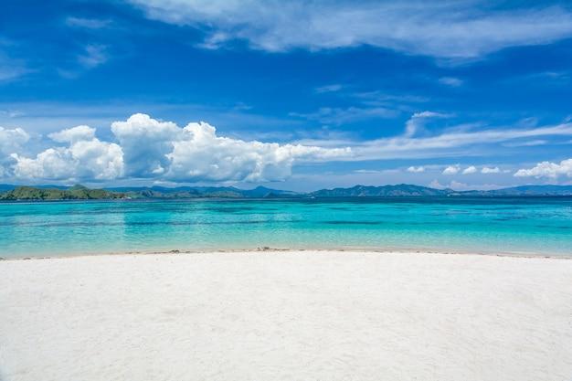 White sand beach avec deux couleurs différentes de clearblue sea à l'île kanawa, komodo Photo Premium