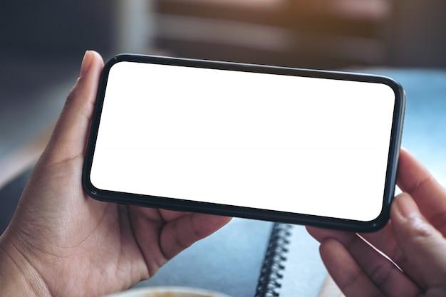 Woman's Hands Holding Et à L'aide D'un Téléphone Mobile Noir Avec écran Blanc Horizontalement Pour Regarder Photo Premium