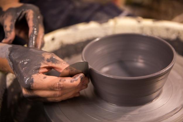 Womens Mains Au Travail Sur Une Roue De Potiers Avec De L'argile Noire Photo Premium